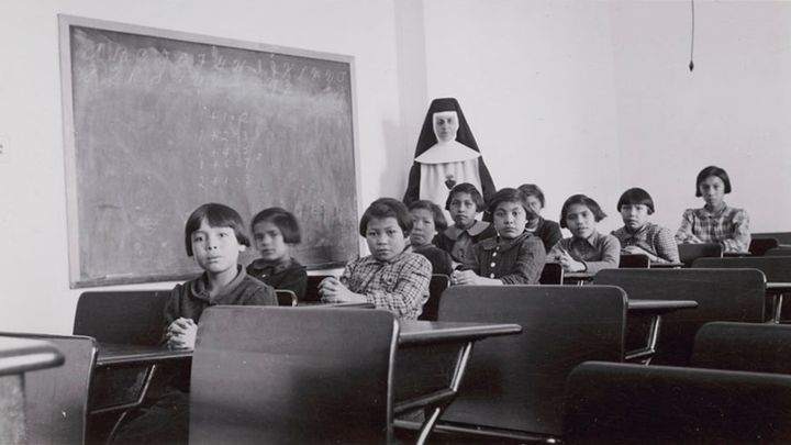 "A group of female students and a nun pose in a classroom at Cross Lake Indian Residential School in Cross Lake, Man. in a February 1940 archive photo. It is estimated that more than 150,000 students attended residential schools under a policy the Truth and Reconciliation Commission amounted to ""cultural genocide."""