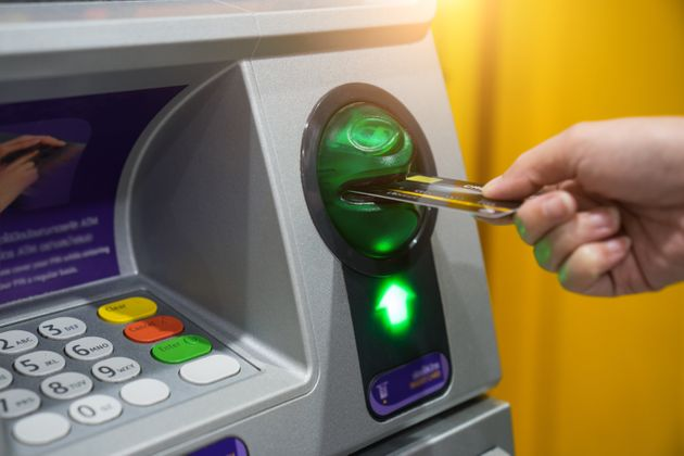 Woman hand is inserting card to atm machine to withdraw or transfer money