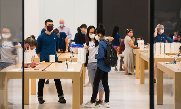 Customers wearing face masks shop at an Apple store in Toronto, Ontario, July 7, 2020. Canada's economic...