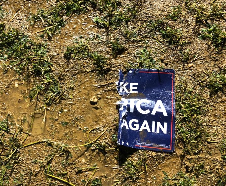 "A torn ""Make America Great Again"" sign sits in the mud on the farm in Lititz, where some 1,000 Trump supporters gathered to w"
