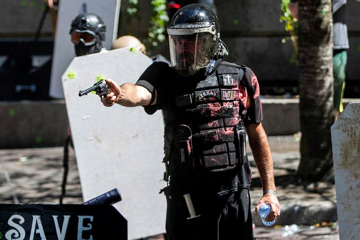 Alan Swinney points a gun during clashes between far-right groups and anti-fascist protesters in Portland, Oregon, on Aug. 22, 2020.