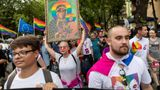 "A participant holds a frame depicting the Virgin Mary with a rainbow halo during the first gay pride organised in Plock, central Poland, amidst risks of disruption by far-rights opponents on August 10, 2019. - In May, police detained in Plock a woman suspected of putting up posters ""desecrating"" an image of the Virgin Mary with a rainbow halo. The frame on the picture shows a likeness of the Black Madonna of Czestochowa, a revered icon of the Virgin Mary located in the devout Catholic country's Jasna Gora monastery. (Photo by Wojtek RADWANSKI / AFP)        (Photo credit should read WOJTEK RADWANSKI/AFP via Getty Images)"