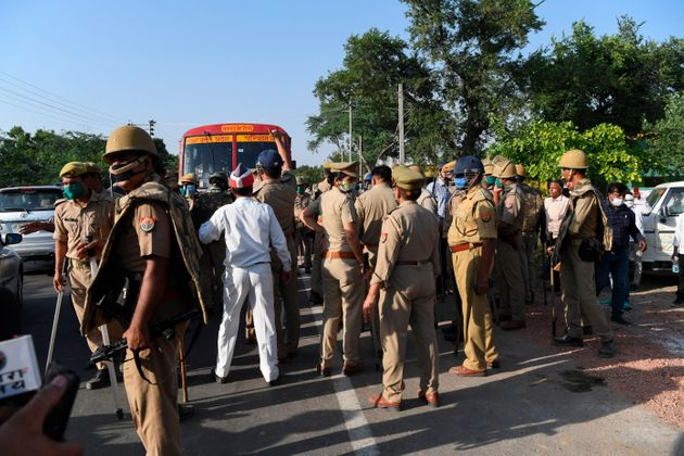 Uttar Pradesh police vacate a road block by Congress party activists outside Bool Garhi village, where...