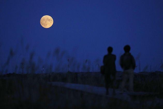 夜空に浮かび上がった中秋の名月を見る人々=2019年9月13日、北海道石狩市