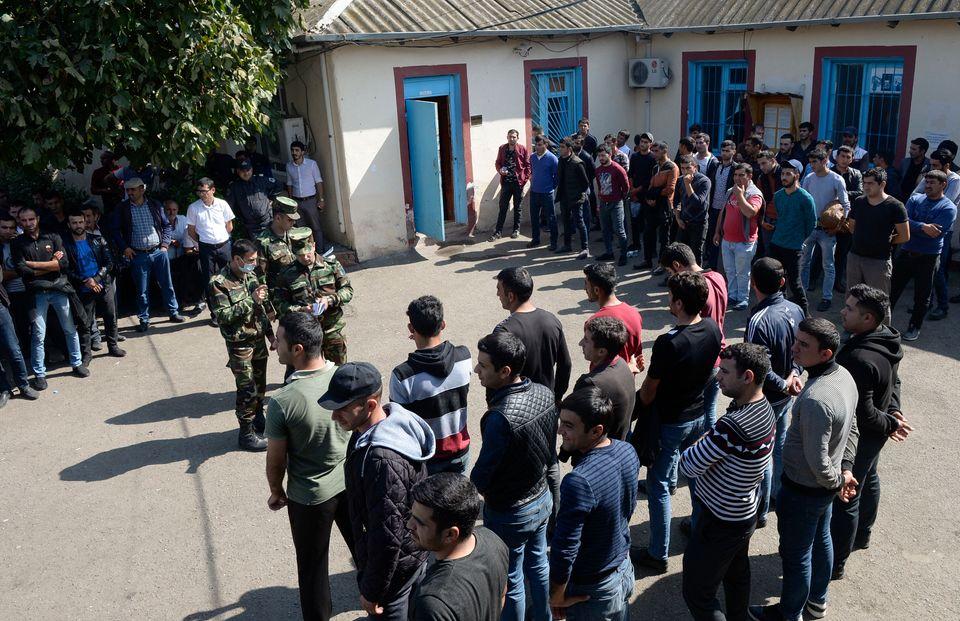 Des hommes se rassemblant dans un commissariat militaire d'une colonie du district de Beylagan, en Azerbaïdjan,...