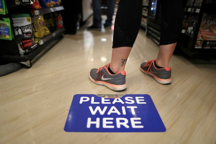 Social distancing decals are seen on the floor of a Ralphs grocery store in Los Angeles.