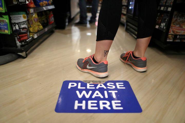 Se ven calcomanías de distanciamiento social en el piso de una tienda de comestibles Ralphs en Los Ángeles.