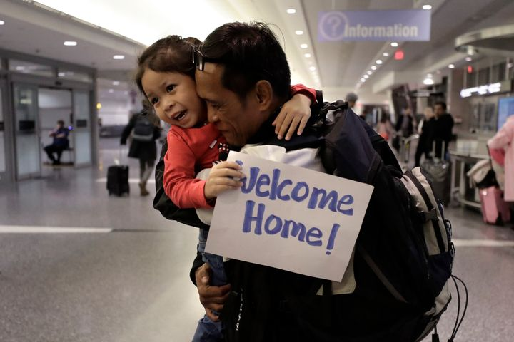 Thy Chea, of Lowell, Mass., center right, hugs his daughter on his arrival at Boston's Logan Airport, Wednesday, Feb. 26, 202