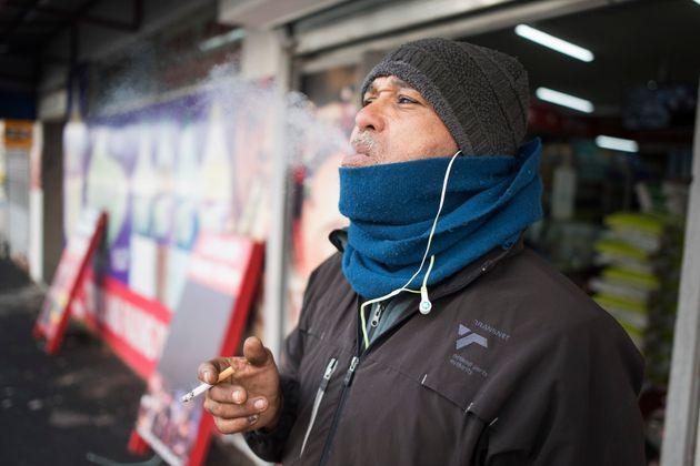 Un hombre fuma a la salida de un
