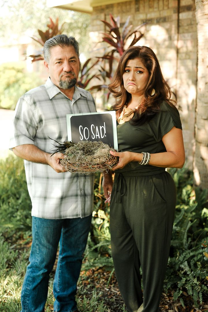 The couple holding up a bird's nest with an accompanying sign.