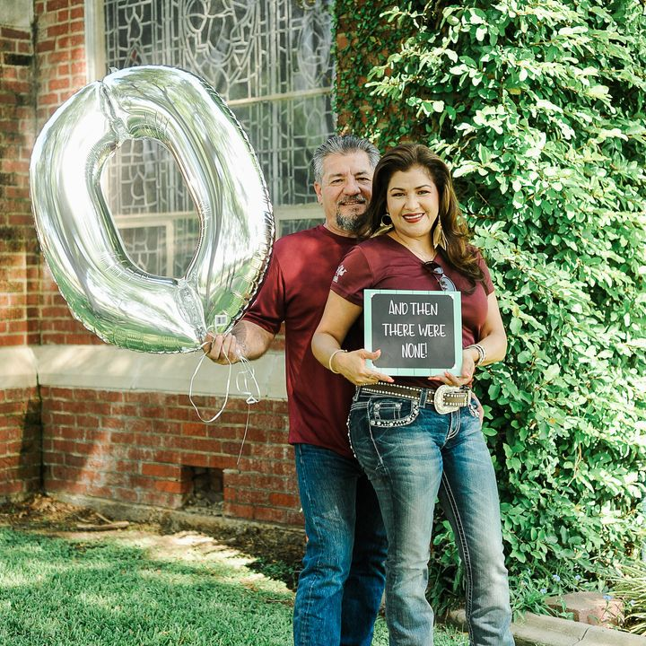 """Juan holds up a zero balloon and Dalila holds up a chalkboard sign that reads: """"And then there were none."""""""