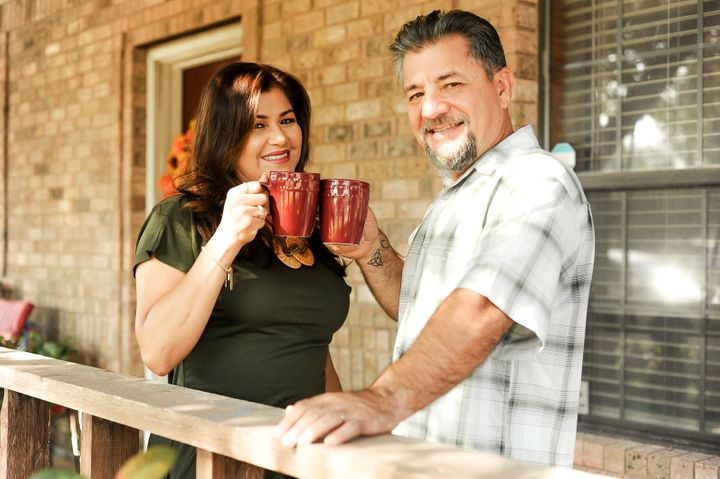 The couple cheers with coffee mugs outside their home.
