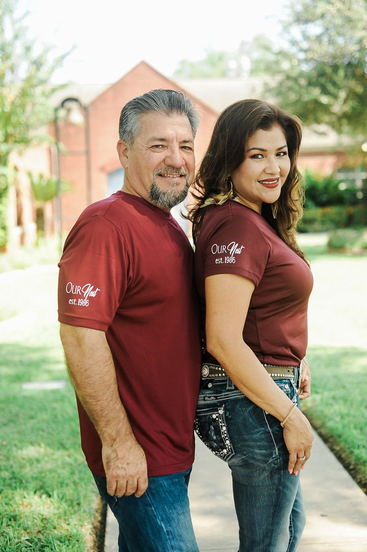 """The couple wearing matching """"Our Nest, Est. 1986"""" T-shirts."""