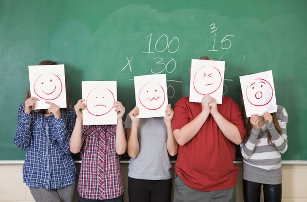 Five students holding faces of different emotions they have from worry to