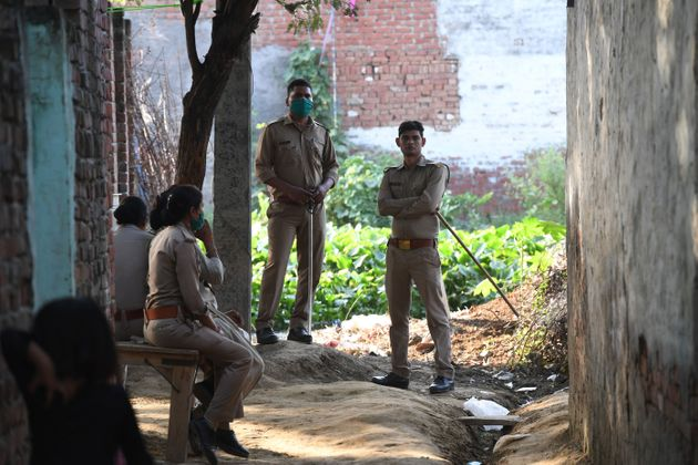 Uttar Pradesh Police personnel stand outside the family house of a 19-year-old woman, who was allegedly...
