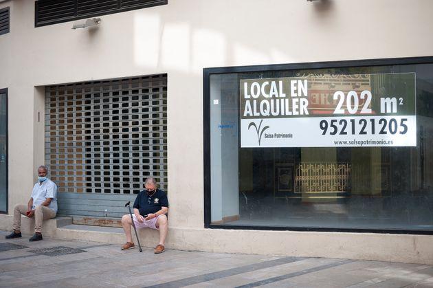 Dos personas mayores sentados en la puerta de una tienda cerrada en