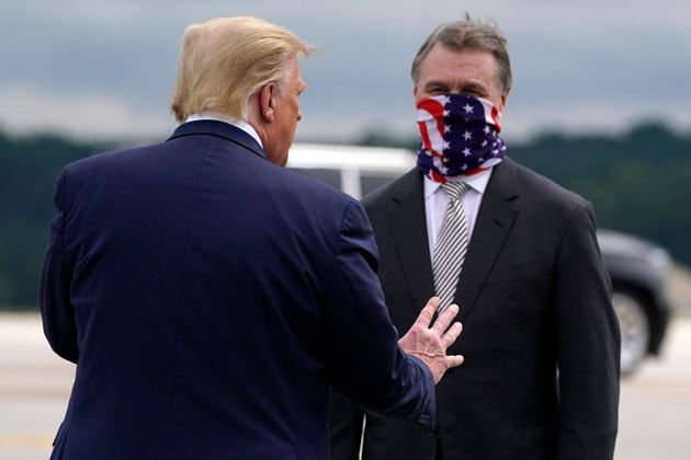 Trump greets Senator David Perdue as he arrives at Dobbins Air Reserve Base for a campaign event at the...