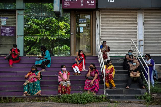 Women who arrived for work await information after the Cochin Special Economic Zone that houses several...