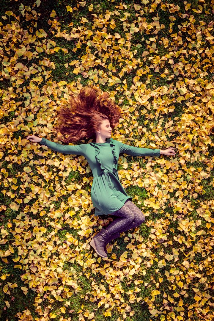 A beautiful woman with red hair in a green dress lies in the autumnal foliage of a ginkgo tree. Copy space for design.