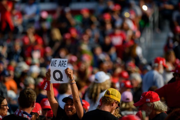 A woman holds up a QAnon sign to the media as attendees wait for President Donald Trump to speak at a Sept. 22 campaign rally
