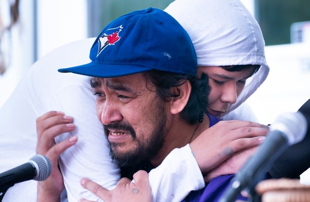 One of Joyce Echaquan's son, Dayvon, hugs his father Carol Dubé as he addressed the media on Friday...