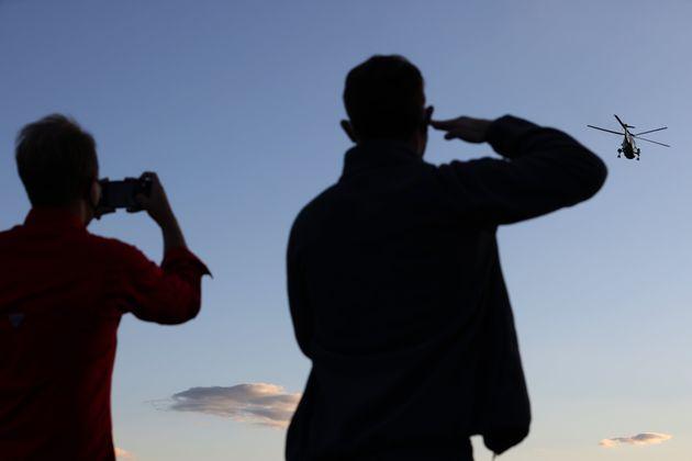 Un hombre saluda al helicóptero presidencial mientras otro inmortaliza el