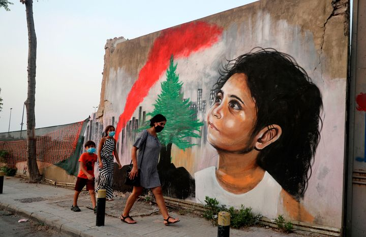 Mask-clad pedestrians walk past a mural painting on September 4, 2020, depicting a young Lebanese girl who suffered a face injury in the August 4 massive blast at the nearby seaport, one month after the disaster that left scores of people dead or injured and ravaged swaths of the capital Beirut. (Photo by JOSEPH EID / AFP) (Photo by JOSEPH EID/AFP via Getty Images)