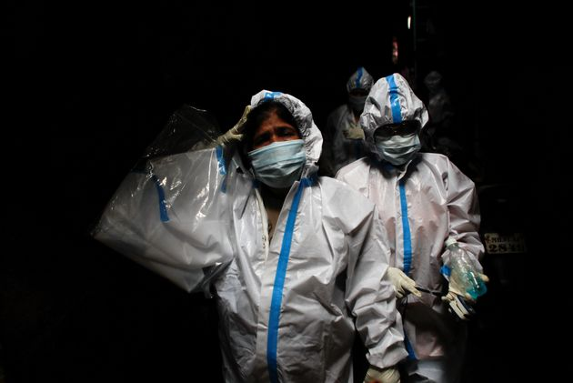 A health worker in personal protective equipment reacts as she and the rest of the team walk through...