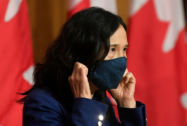 Chief Public Health Officer Theresa Tam removes her mask as she arrives for a news conference on