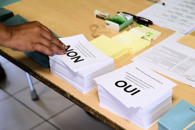 A person picks up a voting form as he prepares to cast his vote at a polling station in the referendum...