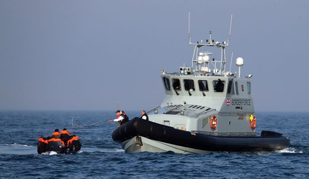 A Border Force vessel assist a group of people thought to be migrants on board from their inflatable...