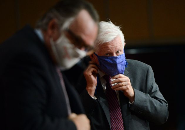 Marc-Andre Blanchard and Bob Rae don masks following a press conference regarding Rae's appointment as...