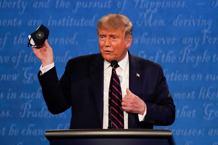 Trump holds up his face mask during the first presidential debate on Tuesday.