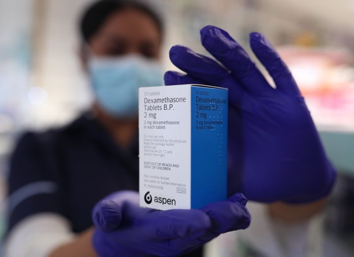 A member of staff at a pharmacy in London holds a packet of anti-inflammatory drug dexamethasone, which has been hailed as a