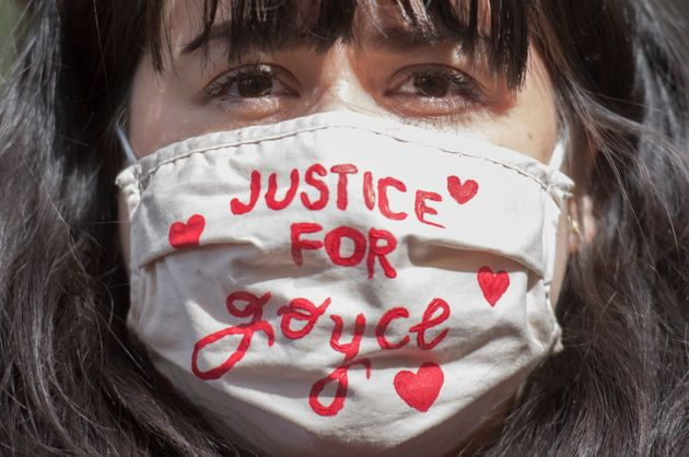 A woman wears a mask as she takes part in a protest on
