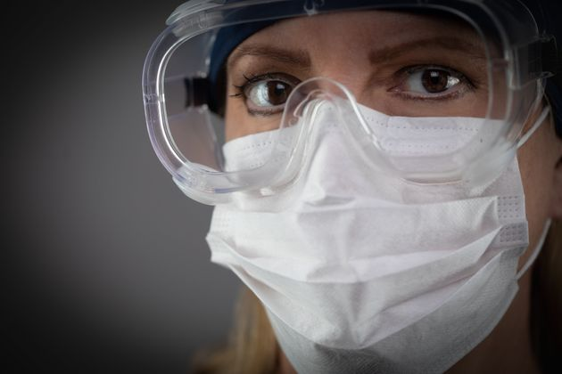 Female Medical Worker Wearing Protective Face Mask and Gear Against Dark