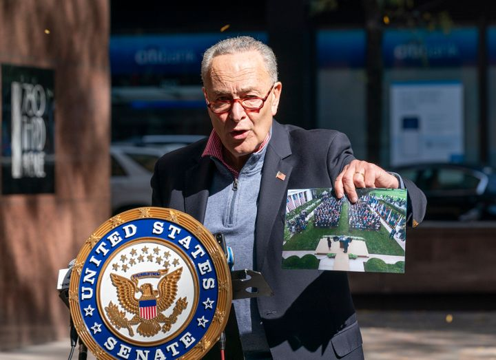 Senate Minority Leader Chuck Senator, speaking in New York City on Oct. 4, holds up a picture of the Rose Garden ceremony whe