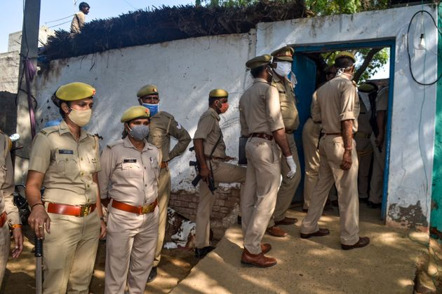 Police personnel near the house of the relatives of the 19-year-old woman in Bool Garhi of Hathras district...