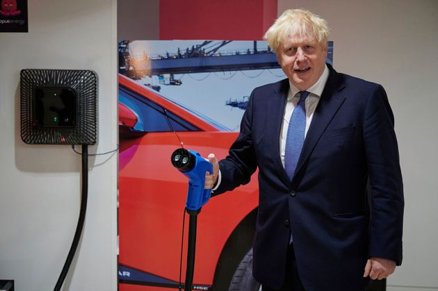 Britain's Prime Minister Boris Johnson holds an electric vehicle charging cable during a visit to the headquarters of Octopus Energy in London.