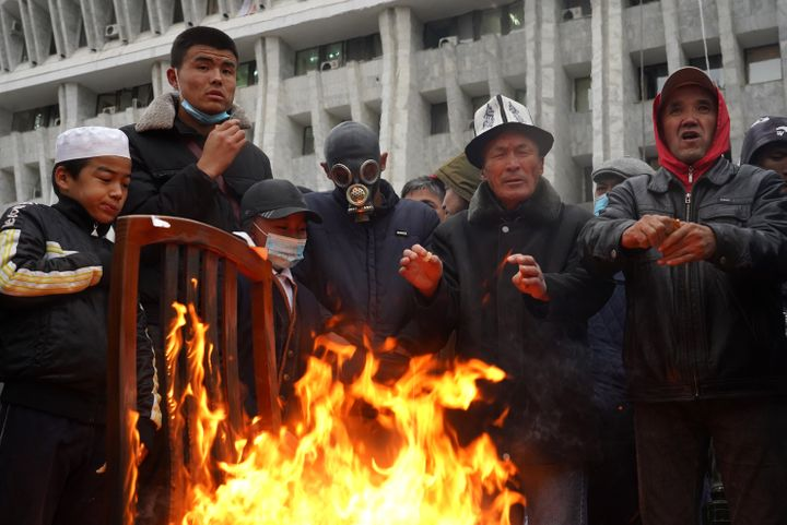 Protesters gather by a bonfire outside the White House building that houses Kyrgyzstan's Presidential Administration and Parliament, seized by participants in protests against the results of the 2020 Kyrgyz parliamentary election.