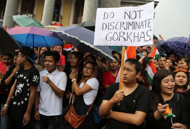 Protestors demanding the creation of separate state of Gorkhaland in India's north-east, stand in rain...