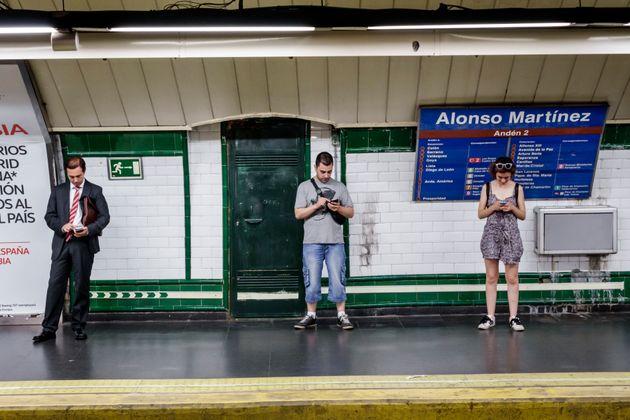 Varios usuarios de metro utilizan sus teléfonos móviles en la estación de Alonso