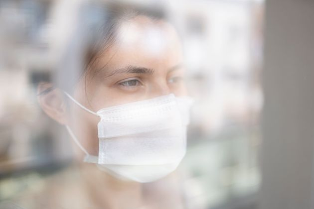 Young woman in quarantine looking through the