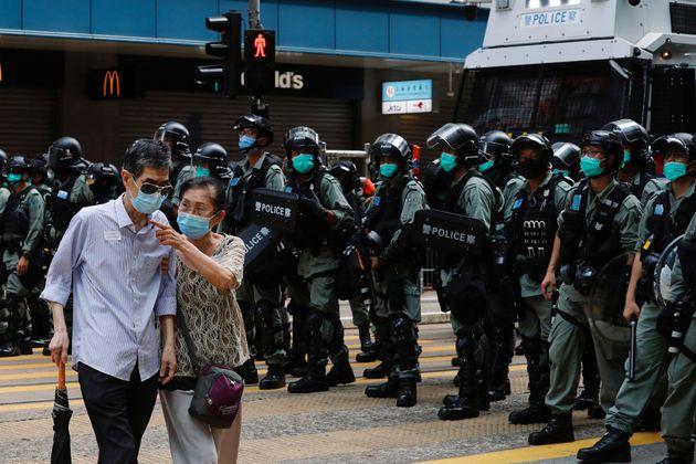 デモの警戒にあたる警察部隊の前を通る通行人=2020年7月