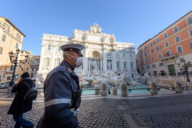 ROME, ITALY - 10 March 2020: A city Police man wearing a face mask walks across the deserted Trevi Fountain...