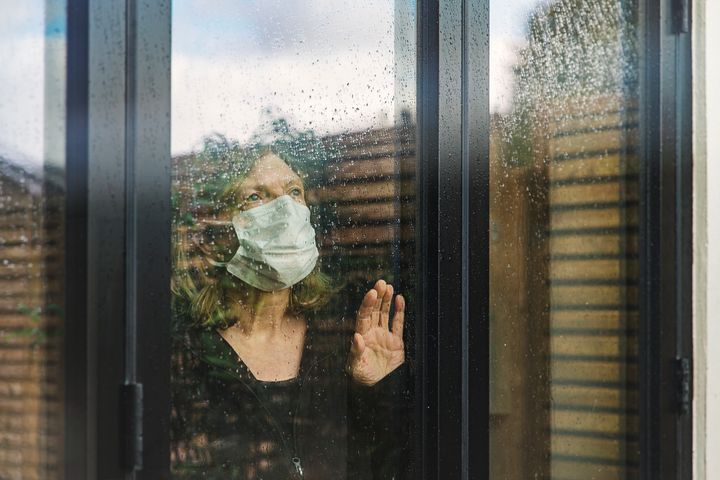 Senior woman with mask looking through window