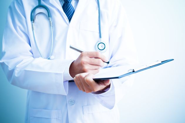 Close-up Of Male Doctor Filling The Medical