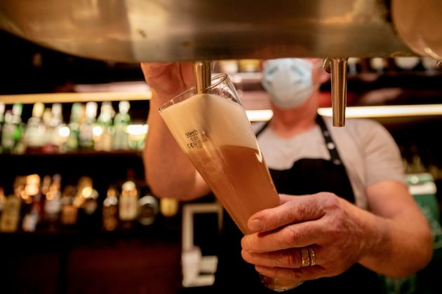 05 October 2020, Berlin: An innkeeper with a mask taps beer into a glass in a pub in the Berlin district...