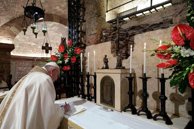 El Papa Francisco firma su nueva encíclica frente a la tumba de San Francisco el 3 de octubre de 2020, en Asís, Italia ...