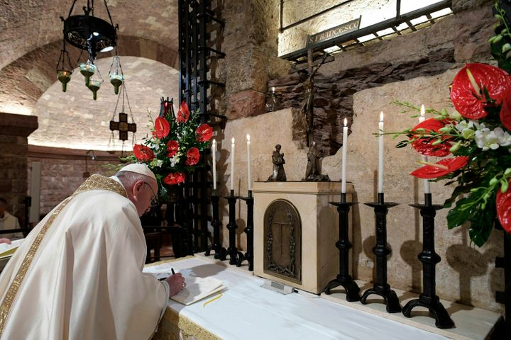 """Pope Francis signs his new encyclical in front of St. Francis' tomb on Oct. 3, 2020, in Assisi, Italy. On the anniversary of the saint's death, Pope Francis celebrated Mass and signed his latest papal letter, """"Fratelli Tutti."""""""